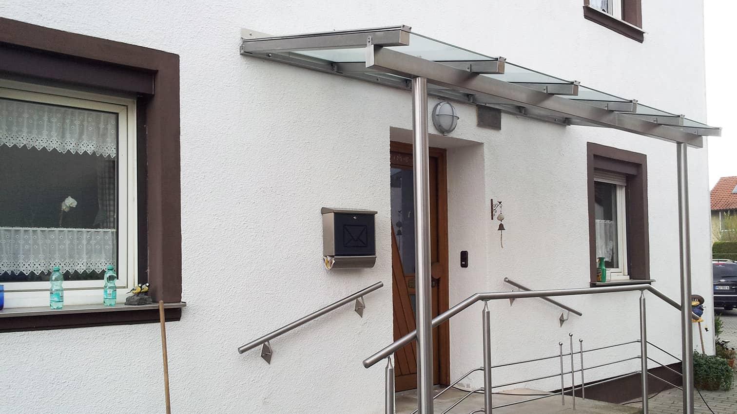 geschützter Eingangsbereich aus Edelstahl mit Glasdach